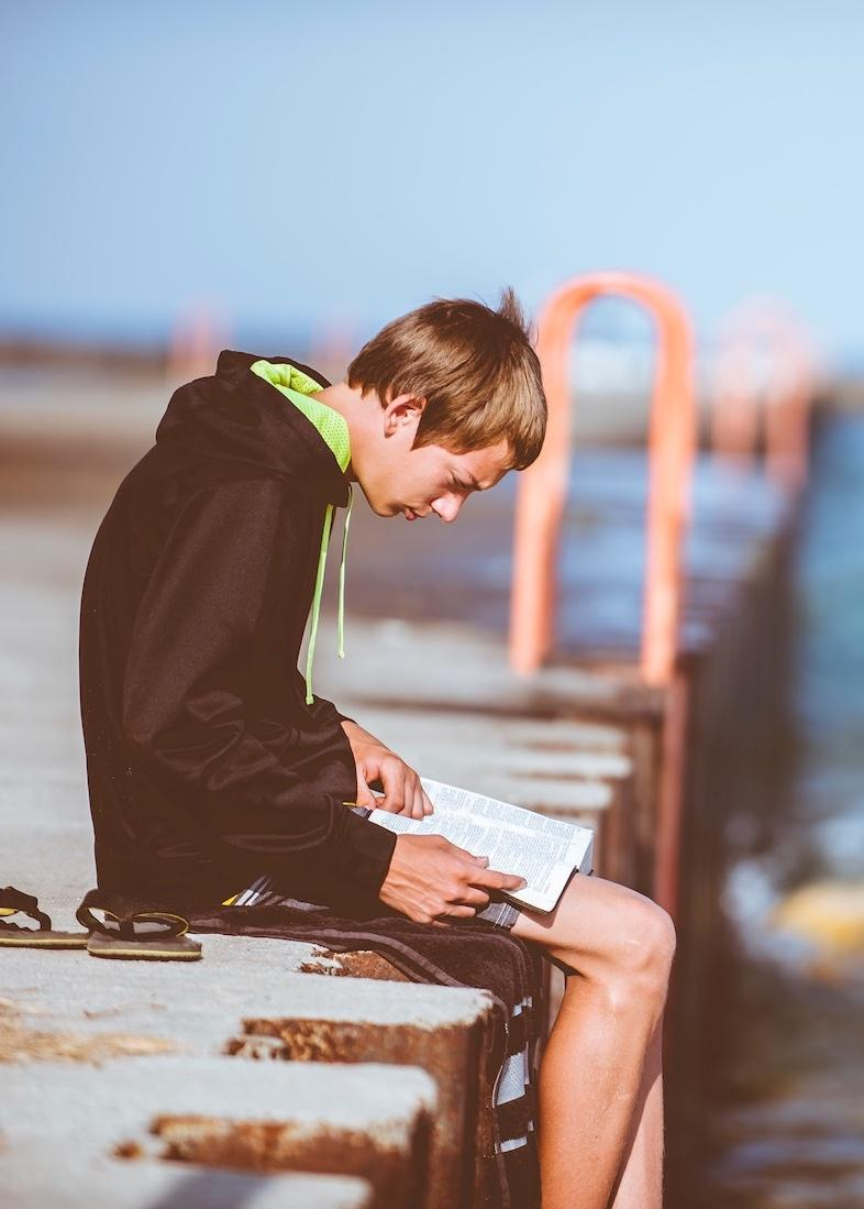 teenage boy struggling with reading on a dock in Vancouver, BC