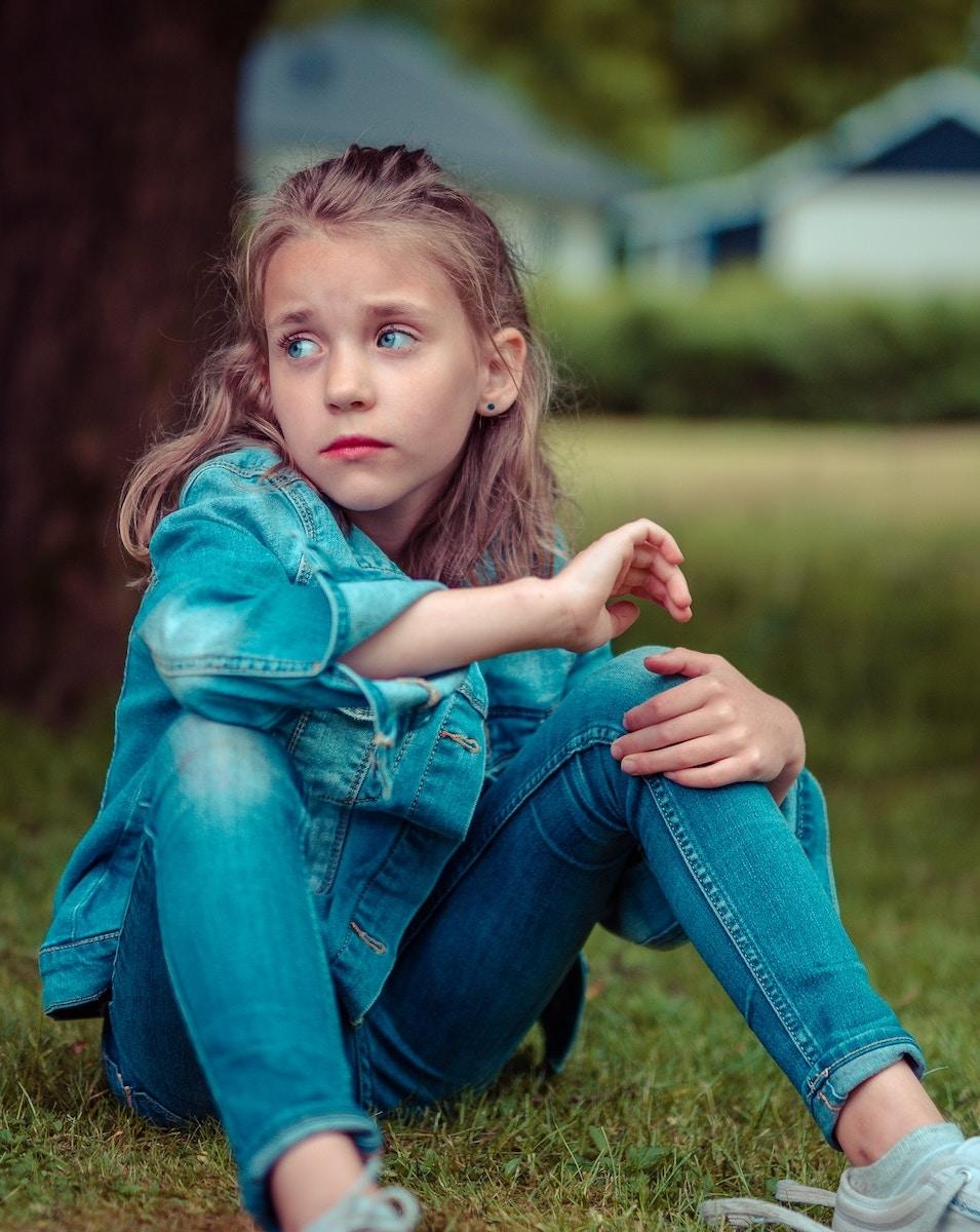 young child sitting on grass, looking concerned, in vancouver bc